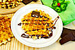 Round Waffle With Chocolate Sauce, Bauble In The Shape Of A Flower With A Ladybug, Slices Of Chocolate, Green Napkin On A Wooden Board stock photo