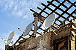 Ruined Building With Stripped Roof Exposing The Roofing Timbers To The Sky And A Row Of Three Satellite Dishes On The Exterior Grungy Wall stock photo