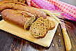 Rye Baguettes On A Board With A Knife, Wicker Basket, Stalks Of Rye, A Napkin On A Dark Wooden Board stock image