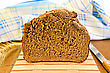 Rye Homemade Bread On A Wooden Stand, A Knife, Ear Of Rye, Blue Checkered Napkin On Wooden Board