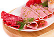Salami, Mortadella And Bacon On Plate On Wooden Board stock photo