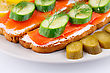 Salmon Sandwiches With Fresh And Pickled Cucumber And Lemon On Plate Closeup Image stock photo