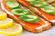 Spread Salmon Sandwiches With Fresh And Pickled Cucumber And Lemon On Plate Closeup Image stock photo