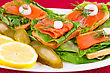 Salmon Sandwiches With Lettuce, Fresh And Pickled Cucumber, Onion, Lemon On Plate stock photography