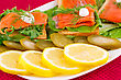 Fishfood Salmon Sandwiches With Lettuce, Fresh And Pickled Cucumber, Onion, Lemon On Plate stock photography