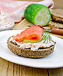Sandwich Of Rye Bread With Cream, Cucumber, Dill And Salmon On A White Plate On A Wooden Board stock photo