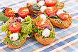 Sandwiches With Rusks, Vegetables, Olives And Feta Cheese On Colorful Tablecloth stock image