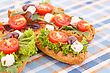 Sandwiches With Rusks, Vegetables, Olives And Feta Cheese On Colorful Tablecloth stock photo