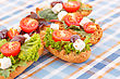Sandwiches With Rusks, Vegetables, Olives And Feta Cheese On Colorful Tablecloth stock photography