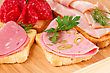 Culinary Sandwiches With Salami, Bacon And Mortadella On Wooden Board stock photo