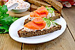 Sandwiches On Two Pieces Of Rye Bread With Cream, Dill, Cucumber And Salmon In A White Plate On A Wooden Boards Background stock image