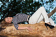 Scared Young Blonde Lying On A Tree Branch