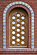 Semicircular Window With A Decorative Wooden Lattice And Ceramic Tiles On The Background Of A Brick Wall stock photo