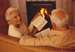 Seniors Senior Couple Reading On Couch By Fireplace stock image