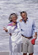 Senior Couple Walking Along Beach stock photo
