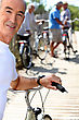 Senior Man With A Bicycle And His Friends In The Background stock photo