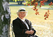 Senior Sitting Under Autumn Tree stock photo