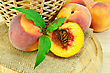 Several Whole Peaches, Half Peach, Twig With Green Leaves, Wicker Basket On A Napkin Of Burlap And Wooden Round Board