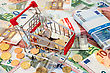 Shopping Cart Full Of Coins, Standing On Euro Banknotes stock photography