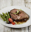Slice Of Beef Roast With Asparagus And Tomatoes stock photo