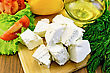 Slices Of Feta Cheese, Sliced Tomatoes, Yellow Bell Peppers, Lettuce, A Bottle Of Oil, Dill On A Wooden Board