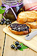 Slices Of Toasted Bread, A Glass Jar With Black Currant Jam, Knife On Background Wooden Board