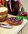 Slices Of Toasted Bread, A Glass Jar With Cherry Jam, Knife On Background Wooden Board stock photo