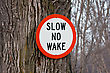 Slow No Wake Sign Nailed To A Tree stock image