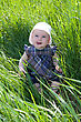 Smiling Small Child Sitting On The Green Grass stock photo
