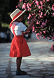 Small Girl In Hat & Red Dress Picking Flowers stock photo