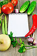 Small Notepad, Red Tomatoes, Pod Red Pepper, Parsley, Garlic, Onion, Two Cucumbers, Green Bean Pods On An Old Wooden Board