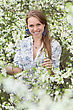 Smiling Blonde Wearing White Blouse Posing In Blooming Garden stock photo