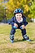 Smiling Little Boy Riding On Roller Skates In The Park stock photo