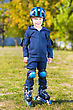 Smiling Little Skater Boy In Blue Sportswear Posing Outdoors stock photo