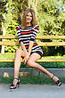 Smiling Pretty Young Blonde Sitting On A Park Bench