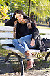 Smiling Pretty Young Woman Sitting On A Bench In Autumn Park stock image