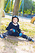 Smiling Skater Boy In Helmet Sitting Near The Tree stock image