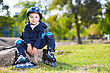 Smiling Skater Boy Sitting On The Stone In The Park stock photo