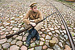 Soldier With Gun And Boiler In Uniform Of World War I, Sit Down And Resting On The Pavement. Costume Accord The Times Of World War I. Photo Made At Cinema City Cinevilla In Latvia