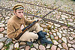 Soldier With Gun And Boiler In Uniform Of World War I, Sit Down And Resting On The Pavement. Costume Accord The Times Of World War I. Photo Made At Cinema City Cinevilla In Latvia. Cockade On The Hat