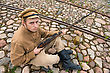 Soldier With Gun And Boiler In Uniform Of World War I, Sit Down And Resting On The Pavement. Costume Accord The Times Of World War I. Photo Made At Cinema City Cinevilla In Latvia. Cockade On The Hat stock photography