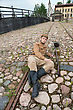 Soldier With Gun And Boiler In Uniform Of World War I, Resting On The Pavement. Costume Accord The Times Of World War I. Photo Made At Cinema City Cinevilla In Latvia