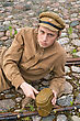 Army Soldier With Gun And Boiler In Uniform Of World War I, Resting On The Pavement. Costume Accord The Times Of World War I. Photo Made At Cinema City Cinevilla In Latvia. Cockade On The Hat Do Not Contai stock photo