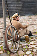 Soldier In Uniform Of World War I, Sit Down, Resting On The Pavement And Smoking. Costume Accord The Times Of World War I. Photo Made At Cinema City Cinevilla In Latvia