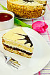 Sponge Cake With Cream And A Fork On A Plate, A Cup Of Tea, Pink Tulip On A White Checkered Tablecloth stock photo