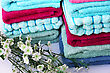 Fold Stack Of Colorful Towelsand Flowers, Closeup Picture. stock photo