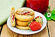 Stack Of Cookies Filled With Jam And Strawberries On A Plate, A Jar Of Strawberry Jam On The Background Of Wooden Boards