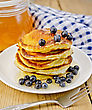 Stack Of Pancakes With Blueberries And Honey On A White Plate, A Jar Of Honey, A Napkin On A Background Of Wooden Boards
