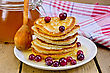 Stack Of Pancakes With Cranberries And Honey On A White Plate With Honey Jar, A Wooden Spoon, Napkin Against A Wooden Board stock image