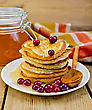 Stack Of Pancakes With Cranberries And Honey, Wooden Spoon On A White Plate, A Jar Of Honey, A Napkin On A Wooden Boards Background